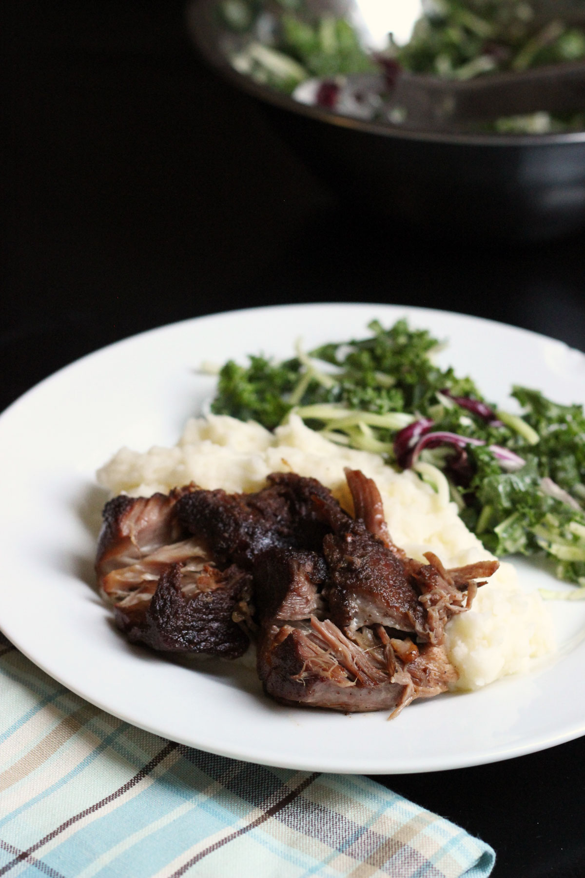 plate of pork, mashed potatoes, and kale