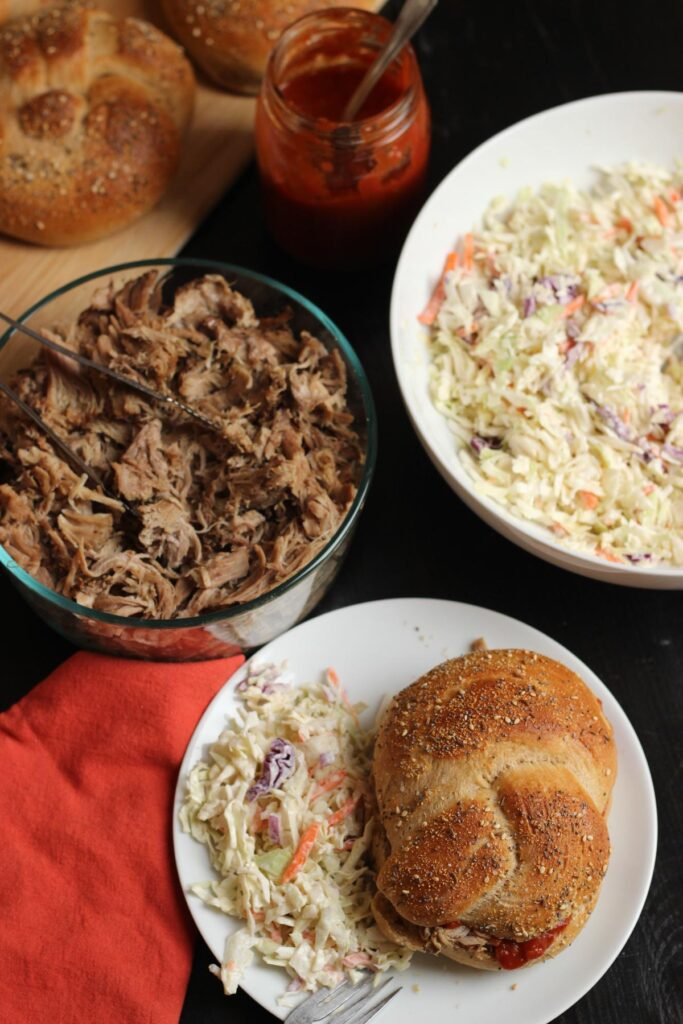 pork sandwich on plate with cole slaw next to bowl of pulled pork.