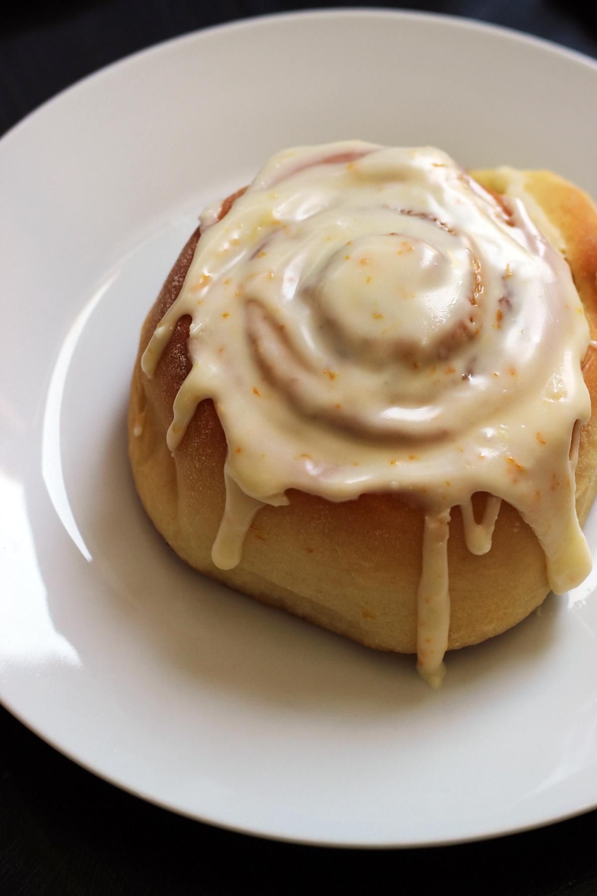 close up of orange cinnamon roll on white plate