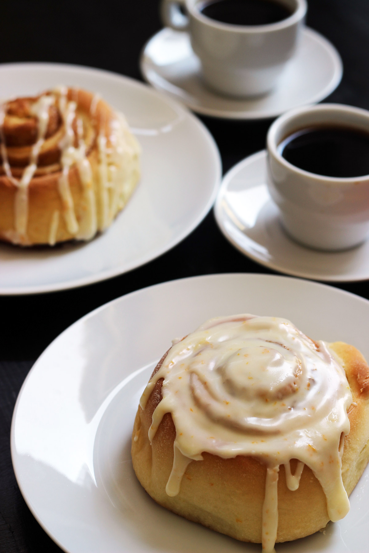 plates of orange sweet rolls with coffees