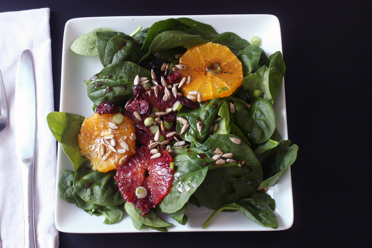 spinach salad on square plate with knife and fork
