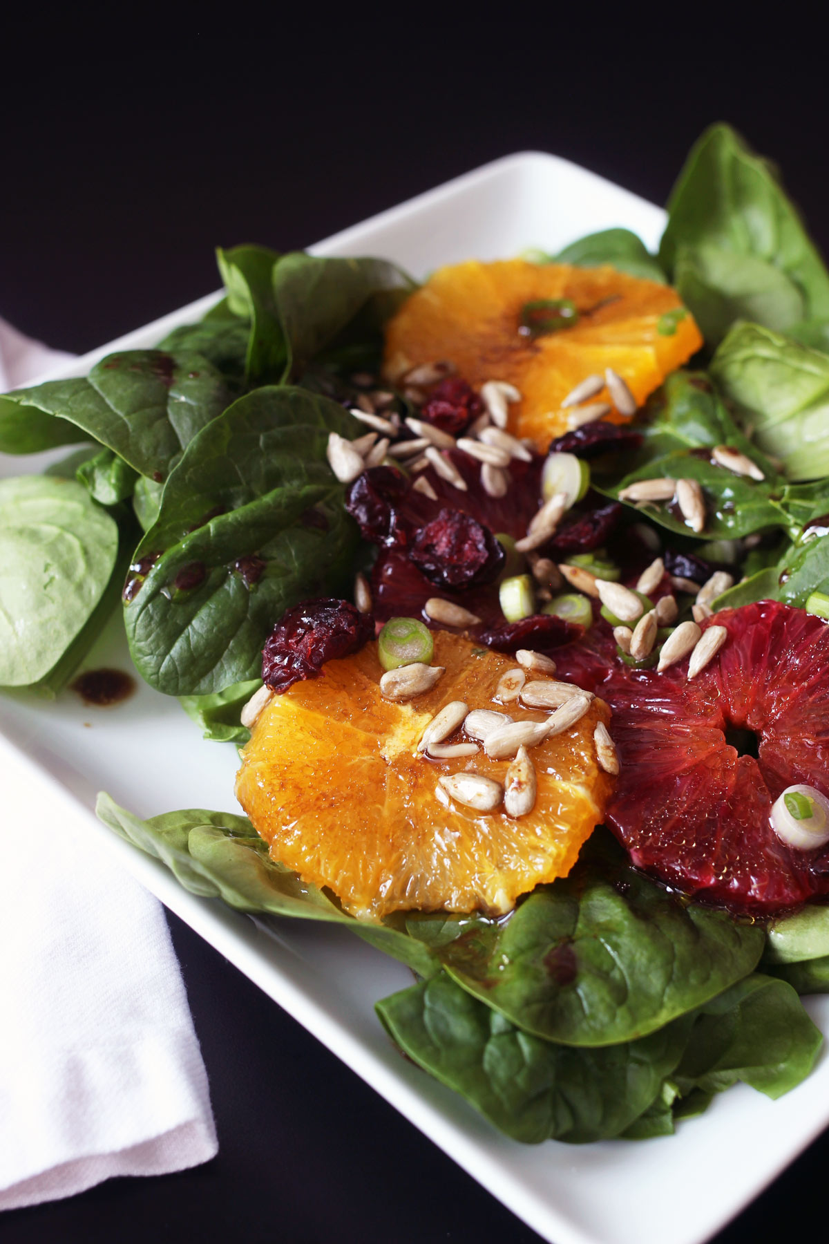 close-up of citrus fruit and sunflower seeds atop a spinach salad on a white plate.