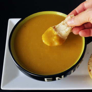 dipping bread in spring vegetable soup