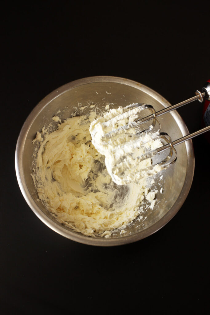 whipped cream cheese in bowl with beaters