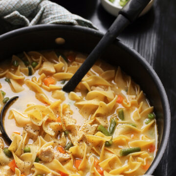 creamy chicken noodle soup in a large black pot with black ladle.