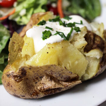 baked potato topped with sour cream and chives