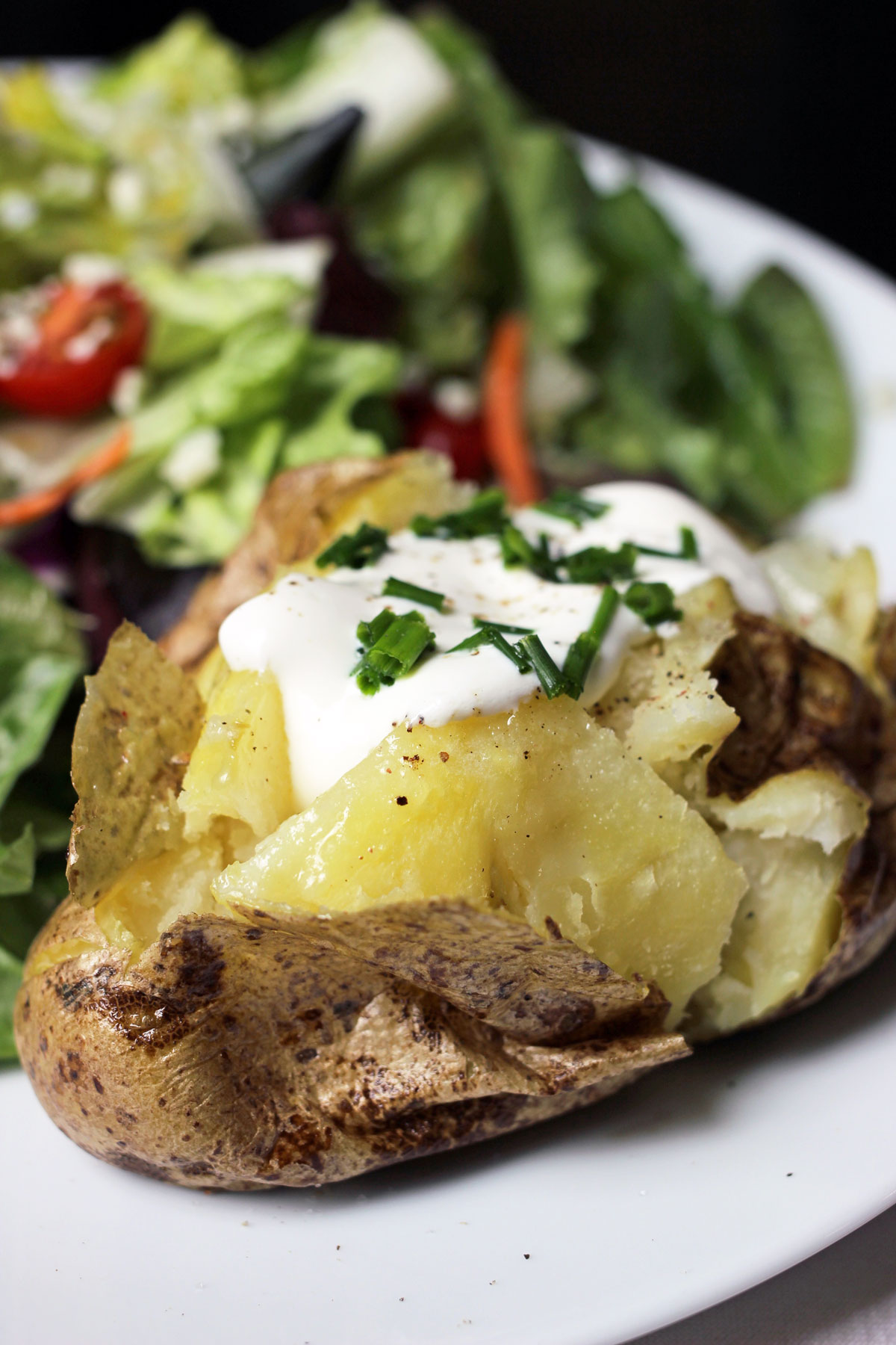 baked potato with sour cream on plate with salad