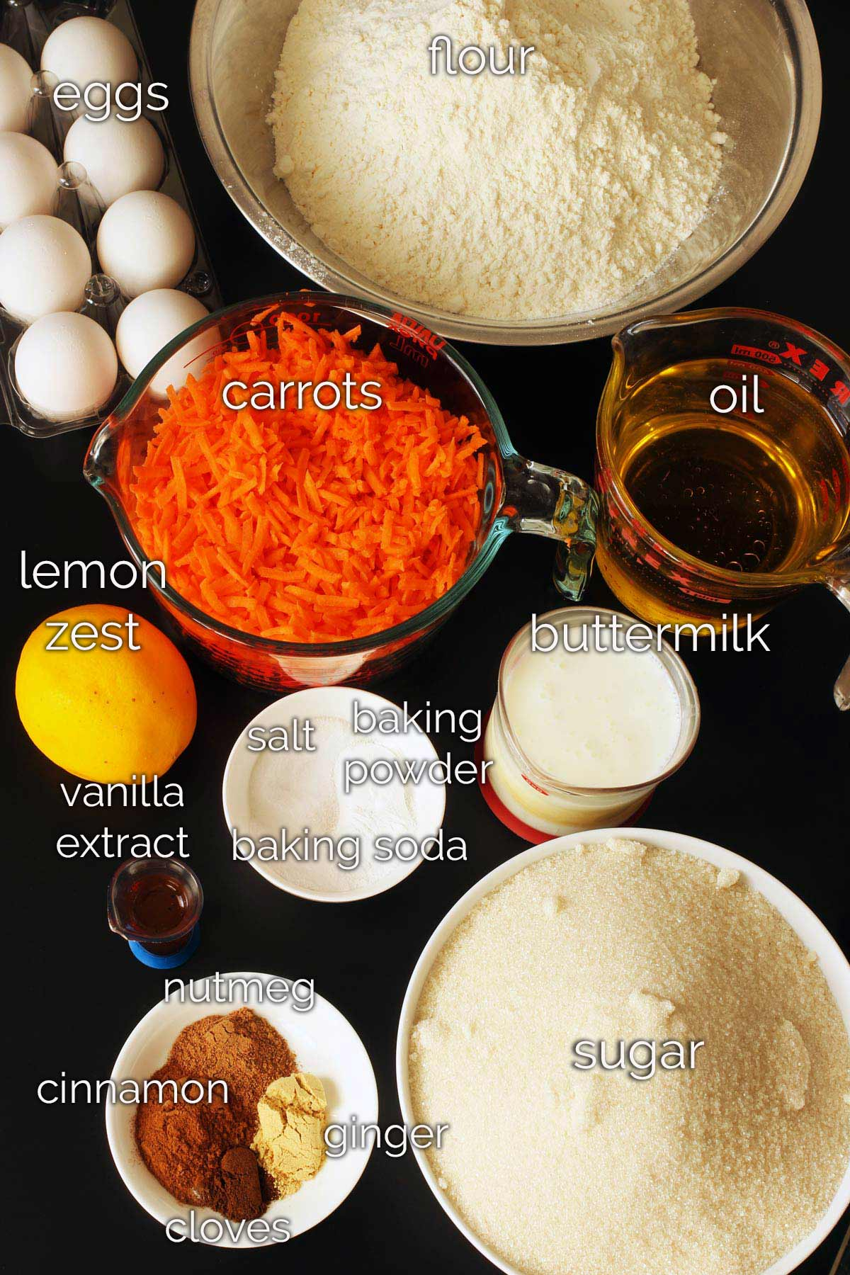 ingredients for carrot bread on black table.