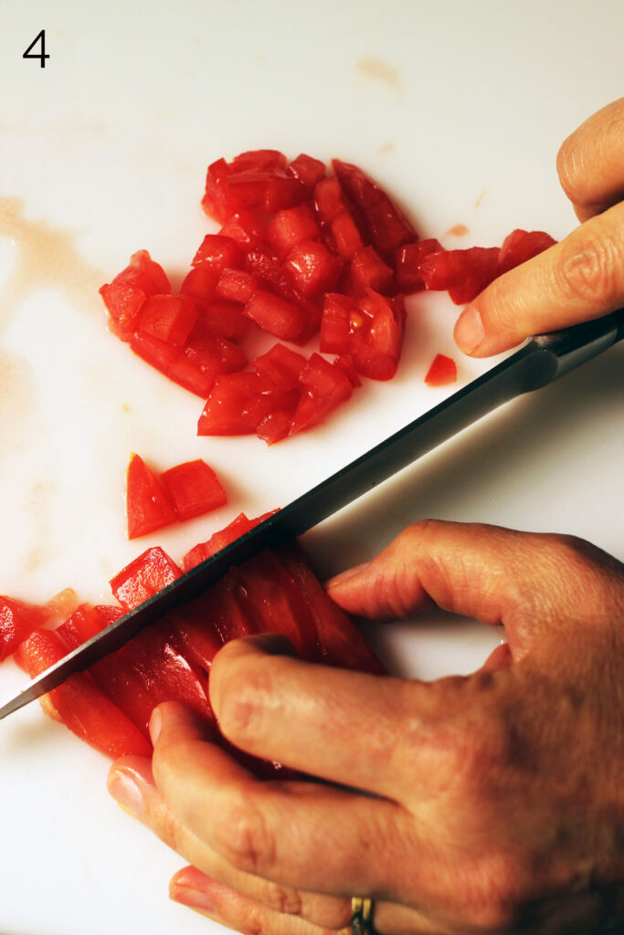 hand cutting the strips of tomato into small dice on cutting board.