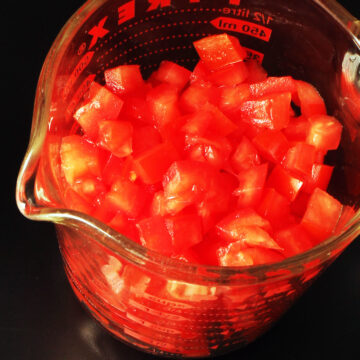 chopped tomatoes in a 2-cup glass measure