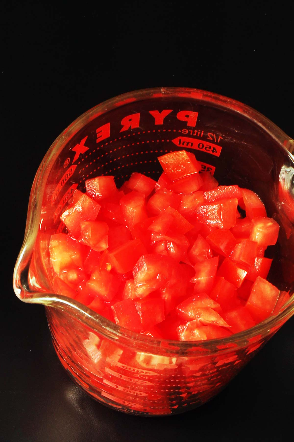 chopped tomatoes in a glass pyrex measuring cup.