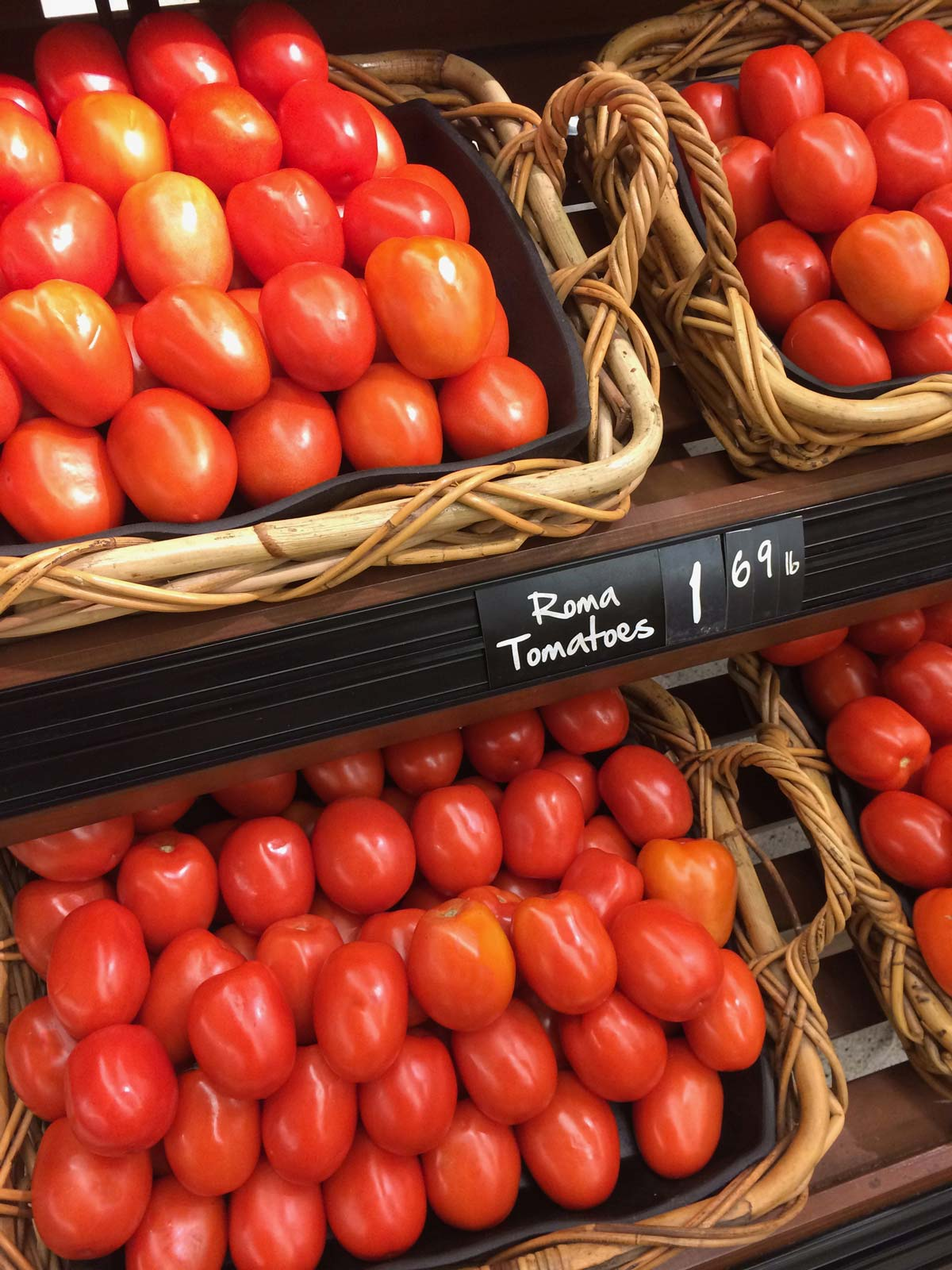 large display of roma tomatoes with price tag at the grocery store.