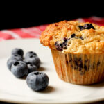 blueberries on white plate next to blueberry muffin.