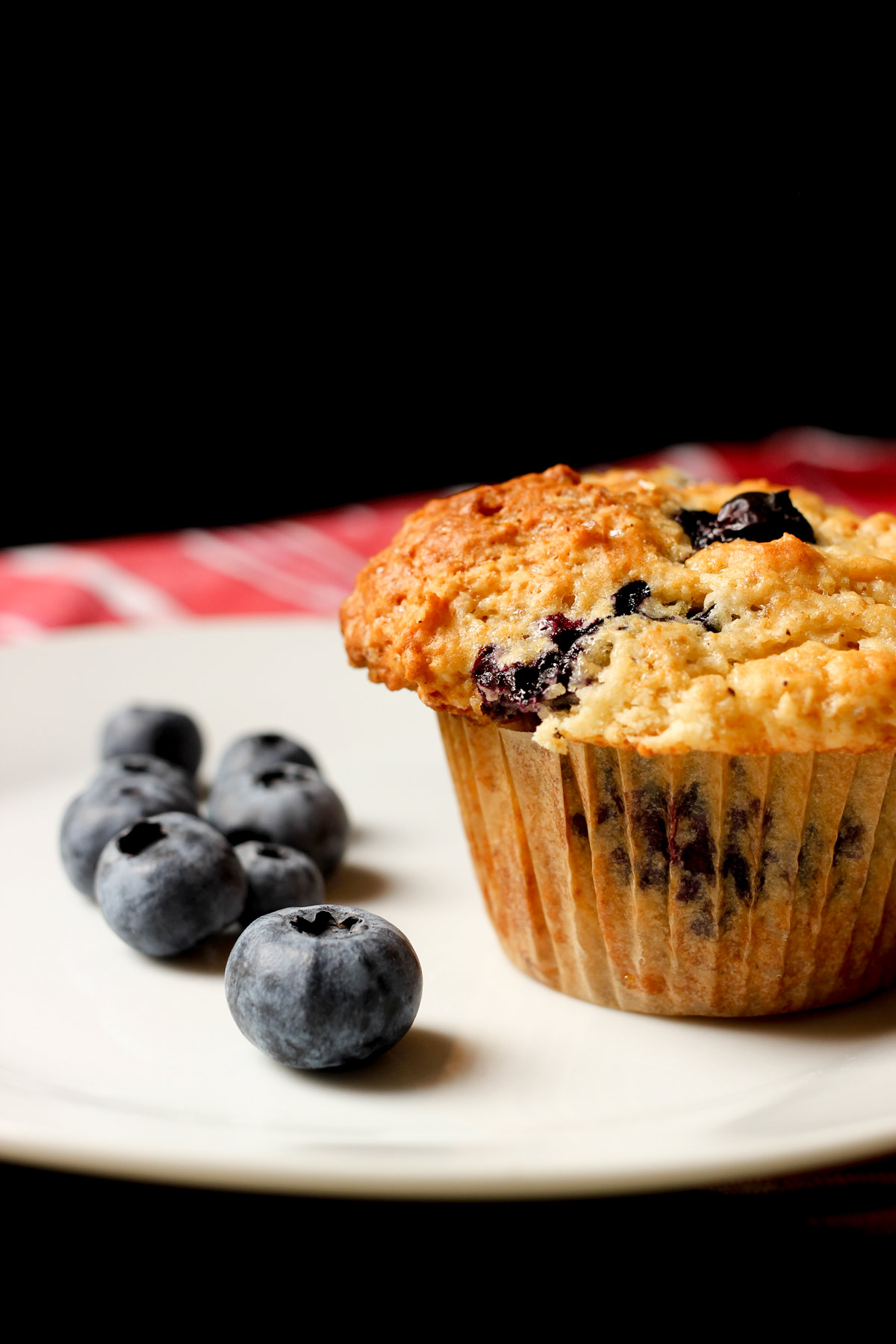 blueberry muffin on white plate with blueberries near a red cloth.