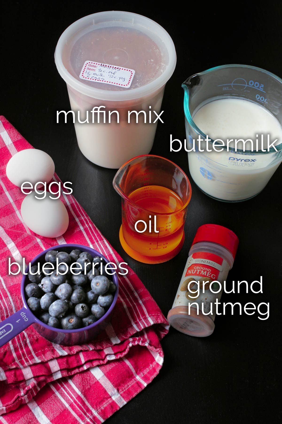 ingredients for blueberry muffins laid out on table on red cloth.