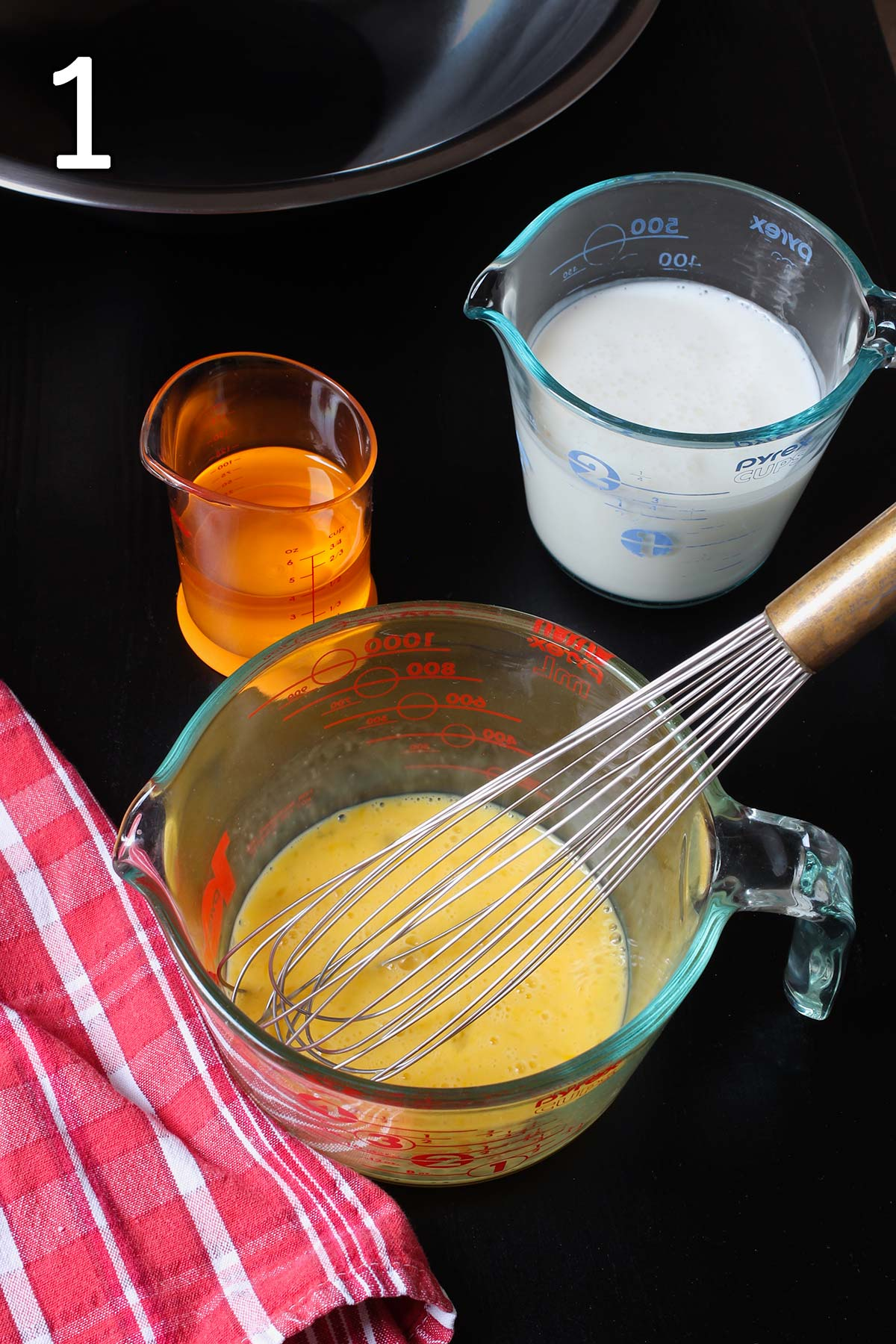 measures of oil, buttermilk, and beaten egg on the table with a red cloth.