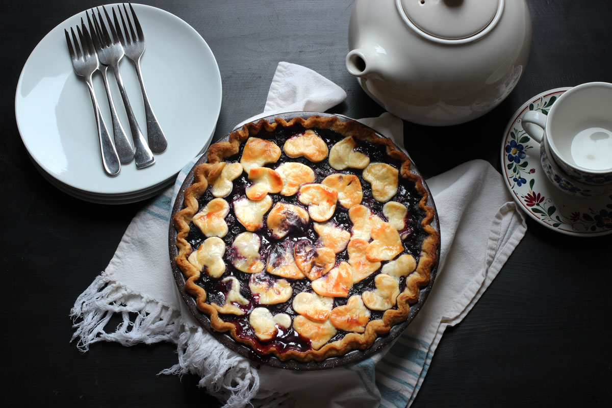 baked blueberry pie on blue towel with tea pot and tea cups, forks, and plates.
