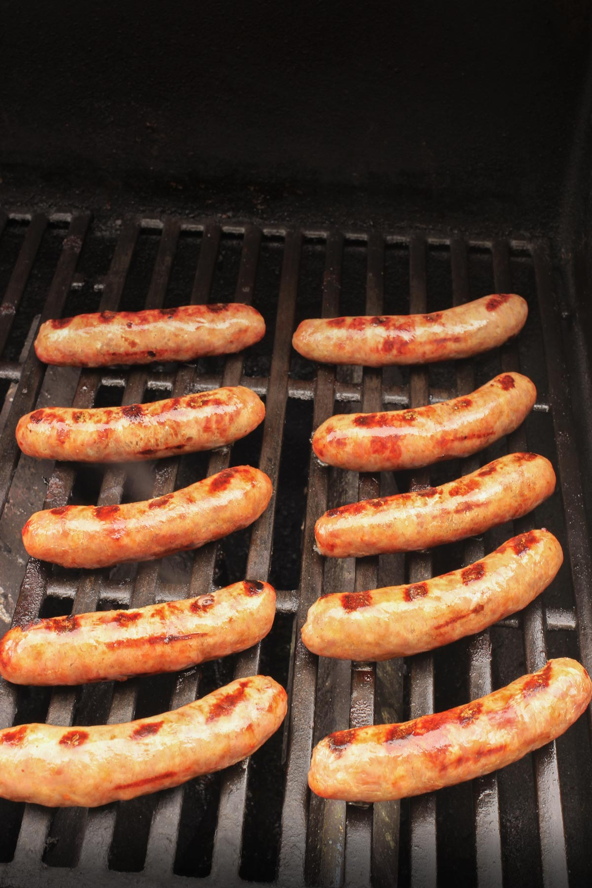 grilled brats lined up on a hot weber grill.