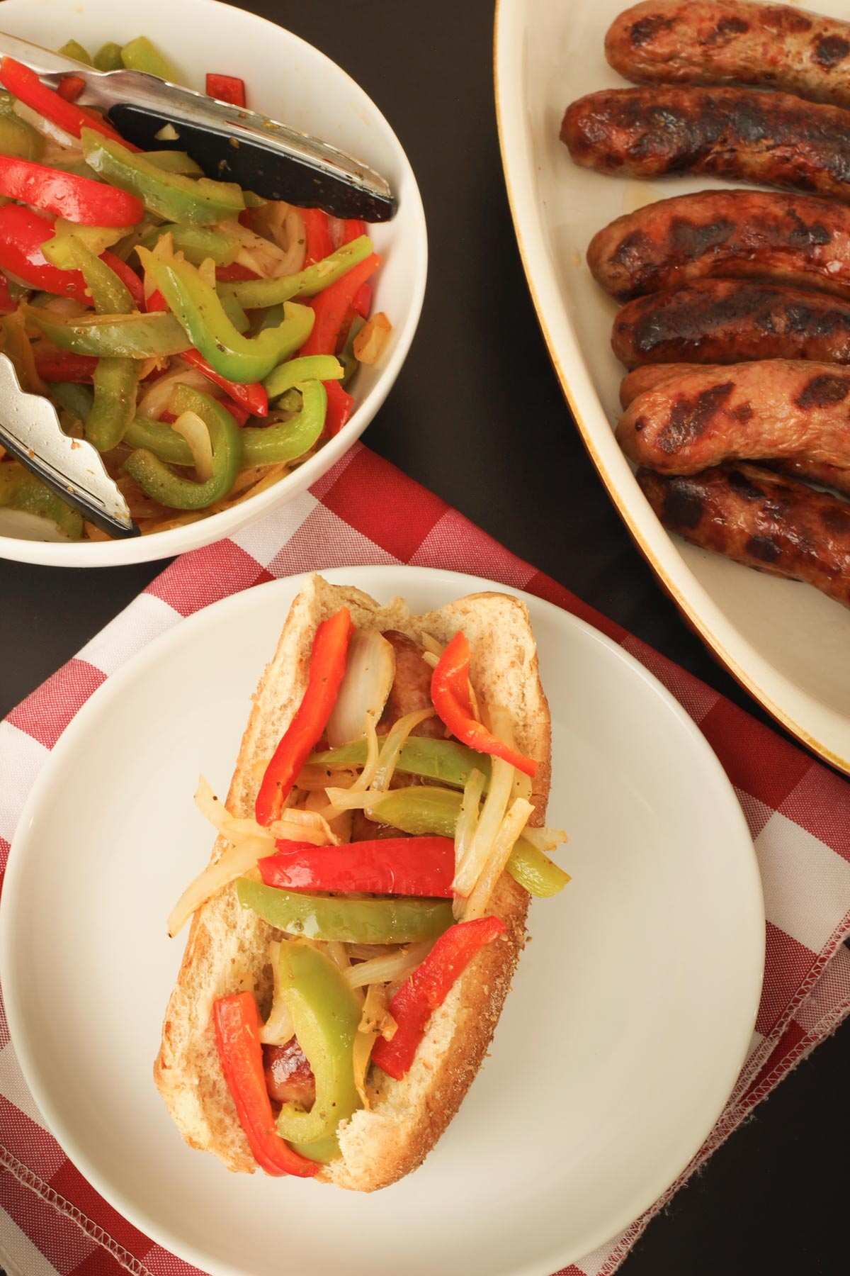 white plate with grilled brat topped with peppers and onions on buffet table with buns and brats.