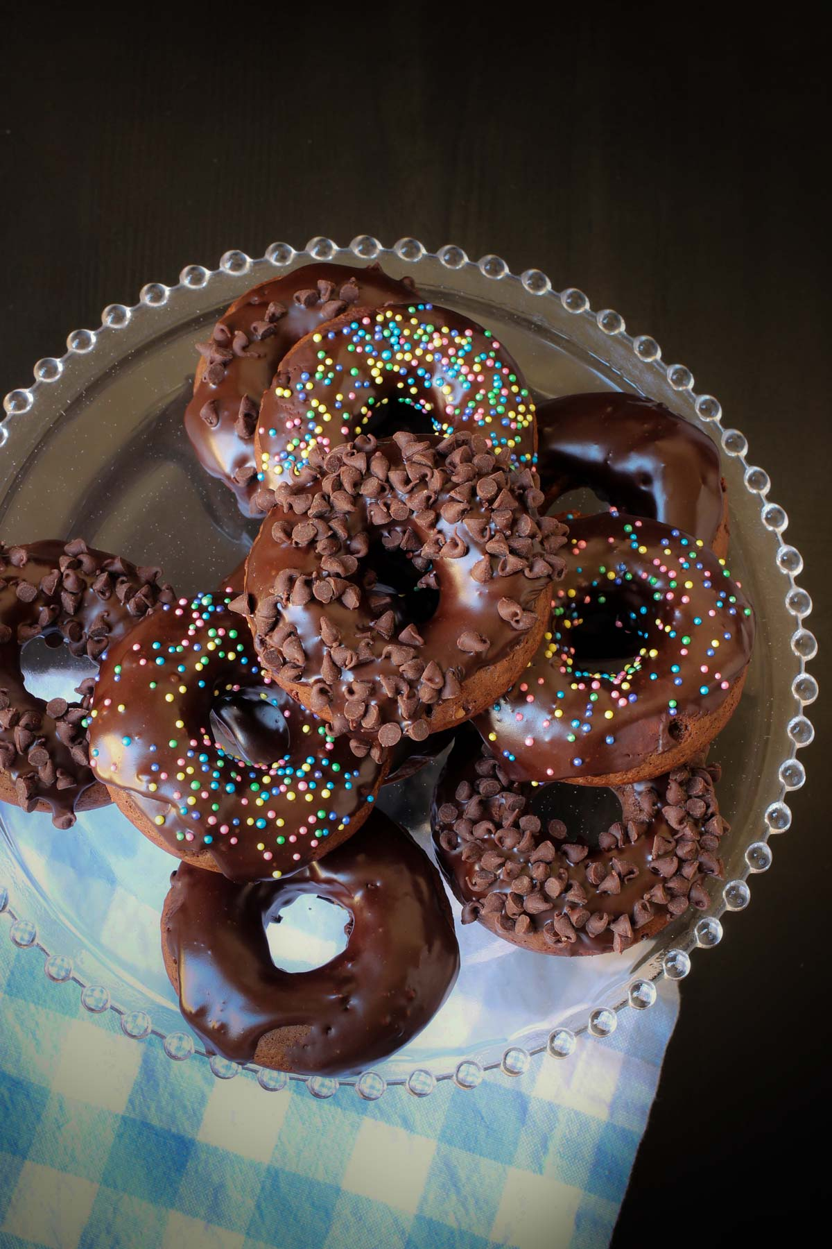 overhead shot of a stack of chocolate donuts on a cake stand with a blue check napkin.