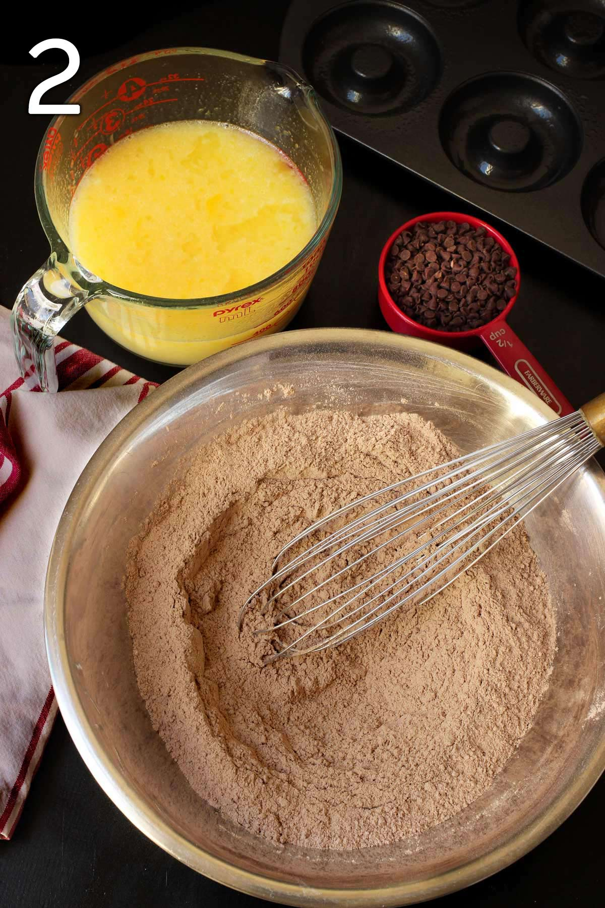 whisking together the dry ingredients in a large metal mixing bowl.