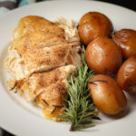 dinner plate with crockpot chicken breast and new potatoes with sprig of rosemary.