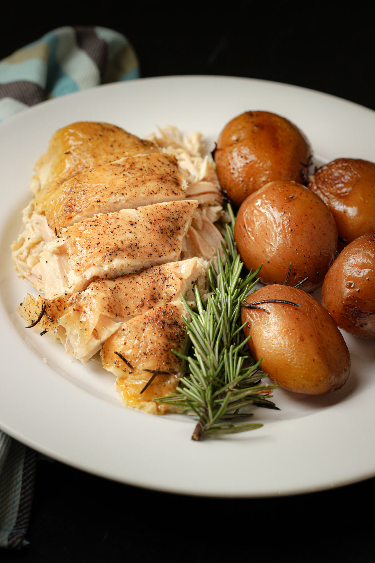 sliced chicken breast on plate with sprig of rosemary and several cooked baby potatoes.