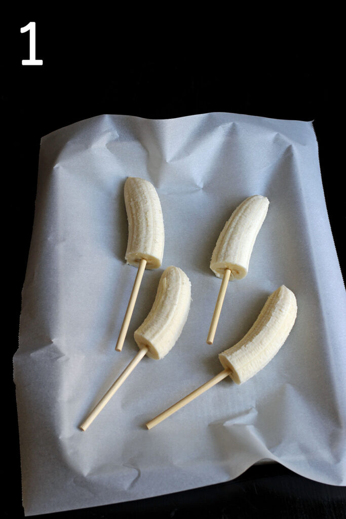 banana halves with lollipop sticks inserted in the bottoms lying frozen on a parchment lined tray.