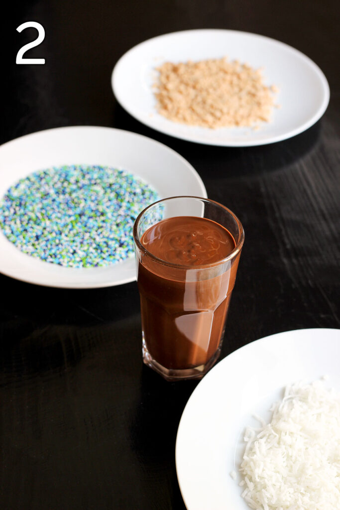 melted chocolate sauce in a tall thin glass with plates of sprinkles and other toppings nearby.