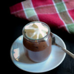 glass pot of chocolate pudding topped with whipped cream on white sauce with spoon.