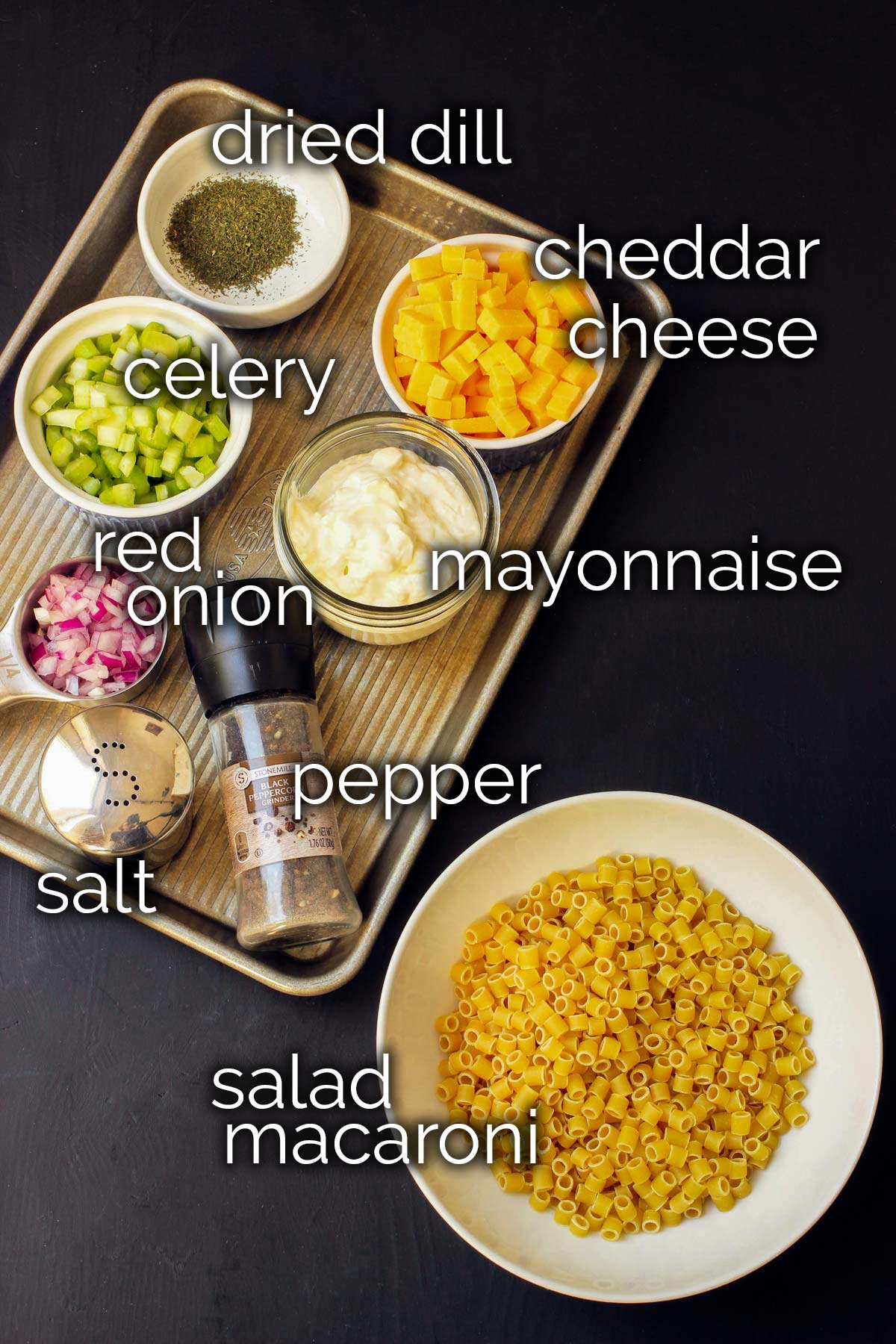 ingredients for macaroni salad laid out on black table.