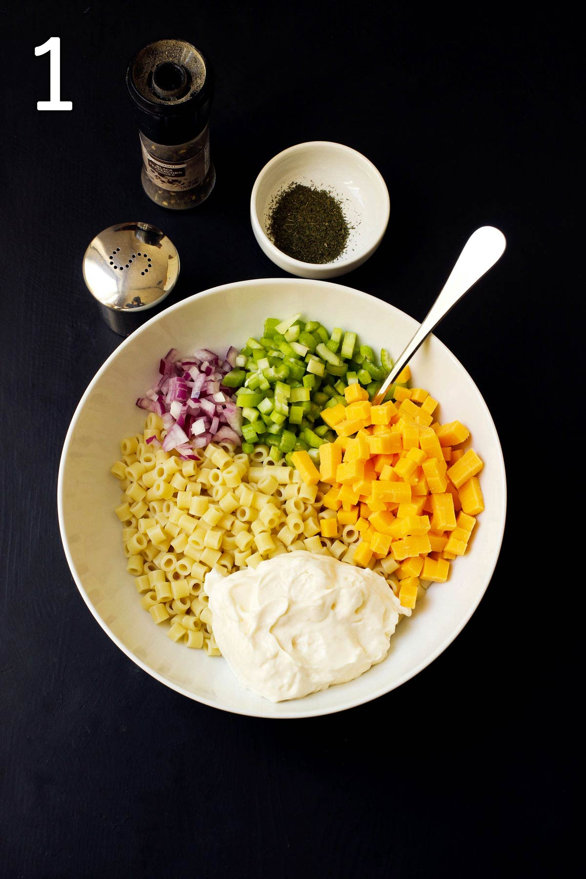 macaroni , mayo, cheese, onion, and celery piled into white mixing bowl.