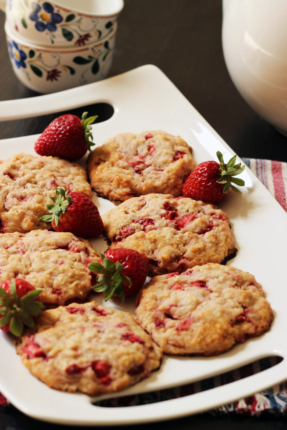 platter of strawberry cookies with fresh strawberries next to stack of teacups and a teapot.