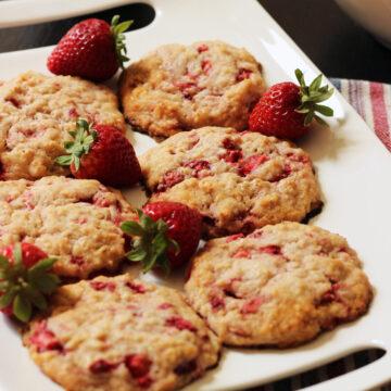 white rectangular platter holding six strawberry oatcakes with fresh strawberries next to them.