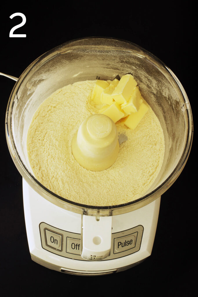 adding butter to the dry mixture in the food processor.