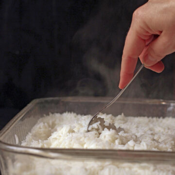 hand holding fork to fluff the baked rice with steam rising.