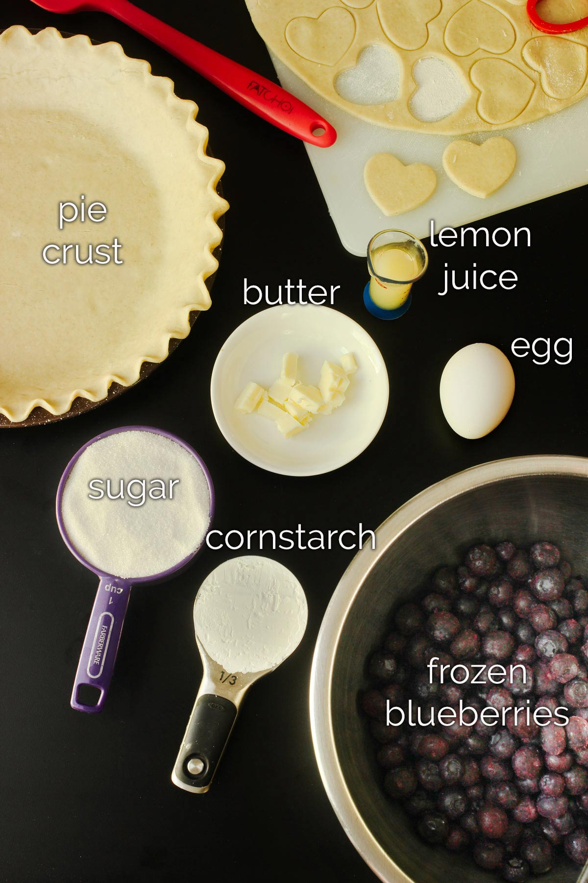 ingredients for blueberry pie laid on table.