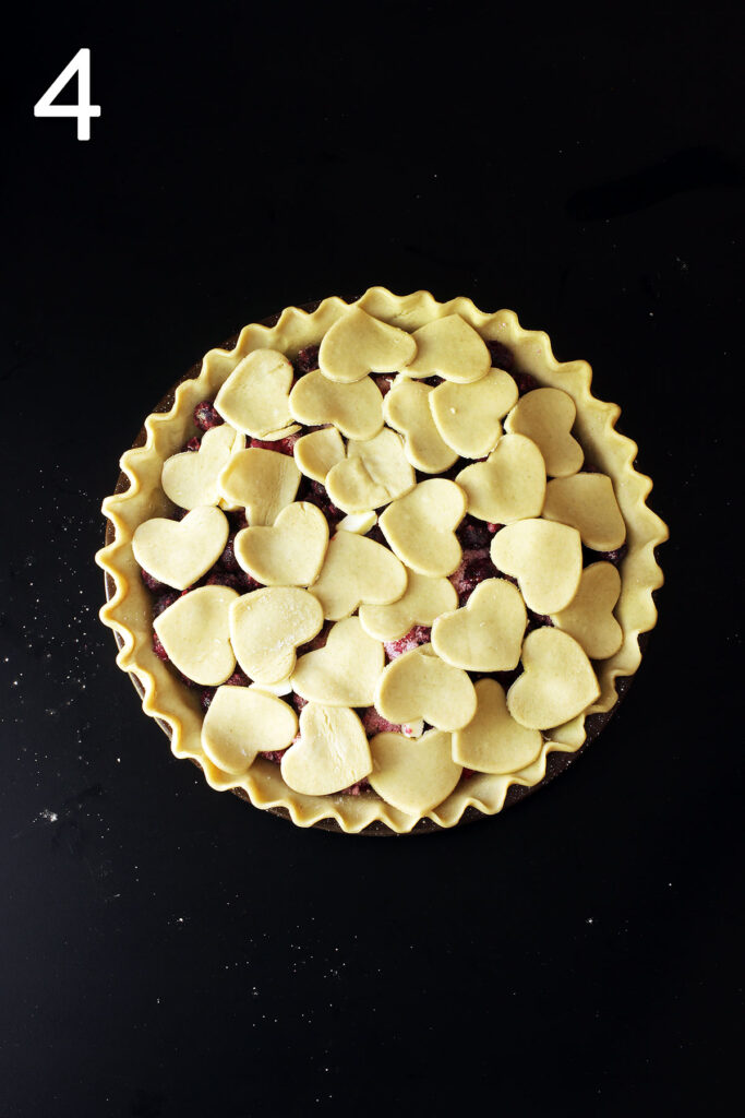 heart cutouts of pie crust layered atop the blueberry pie filling in pie crust.