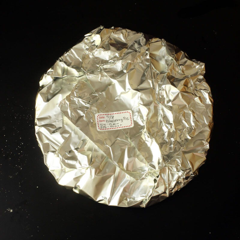 blueberry pie wrapped in foil for freezing.