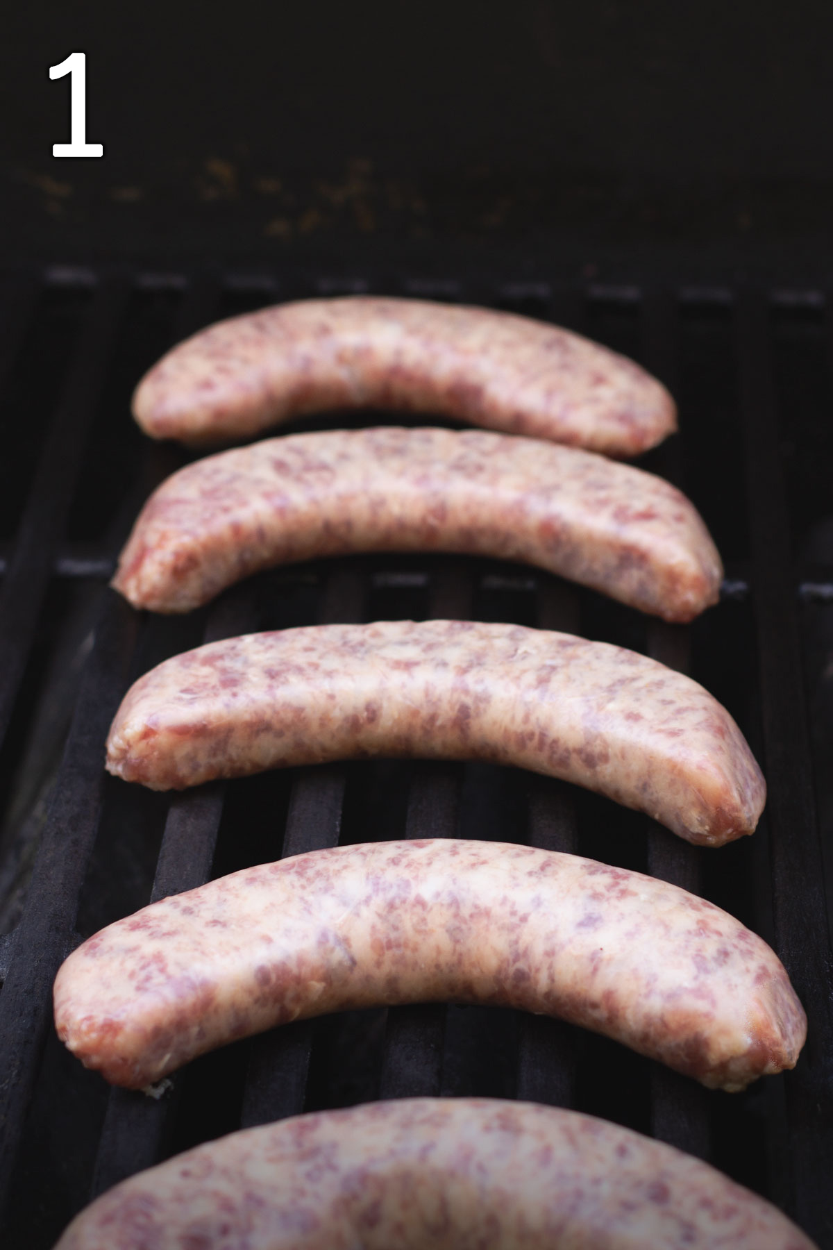 uncooked brats laid out on the hot grill.