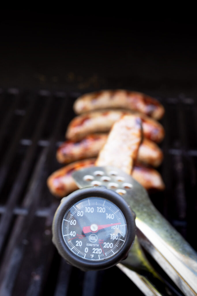 meat thermometer inserted into a brat, approaching 160 degrees.