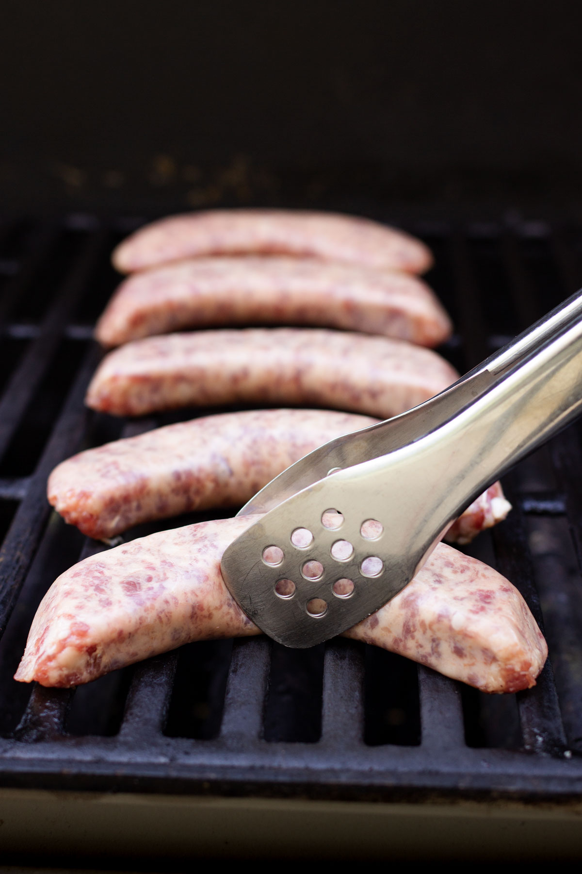 turning the brats with tongs on the hot grill.