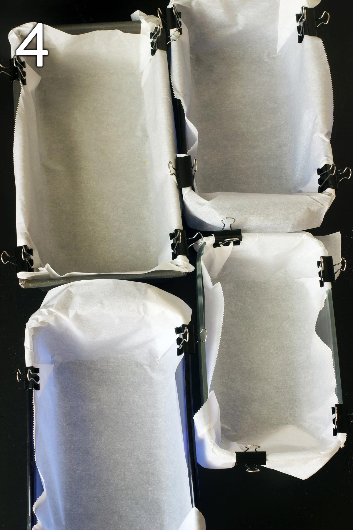 bread loaves lined with parchment paper held with clips.