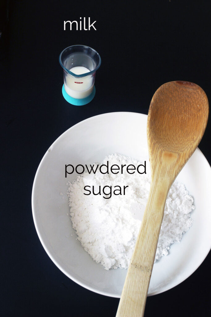 bowl of powdered sugar with measure of milk and wooden spoon.