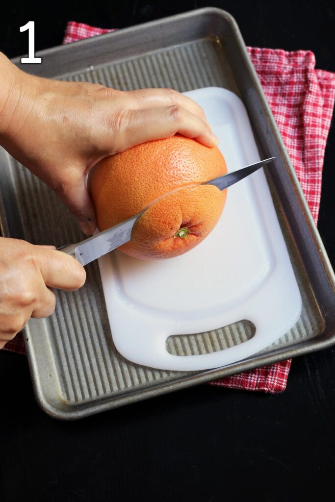 cutting off the end of the grapefruit with a knife.