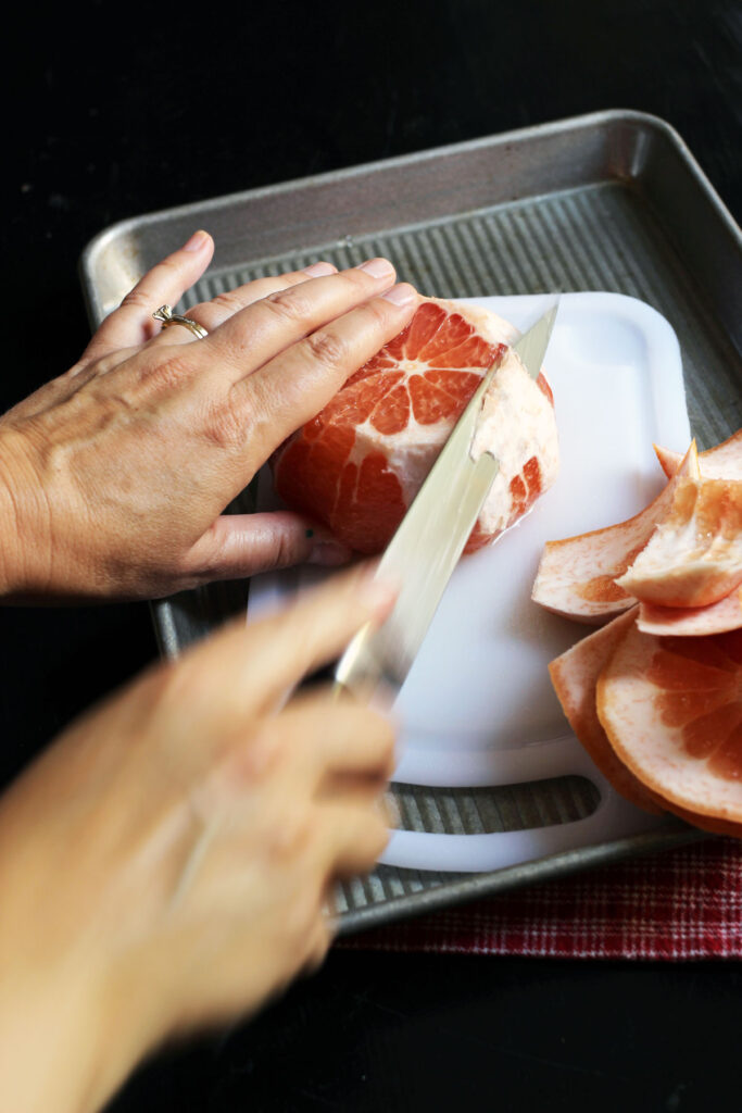 cutting away remaining pith from grapefruit.