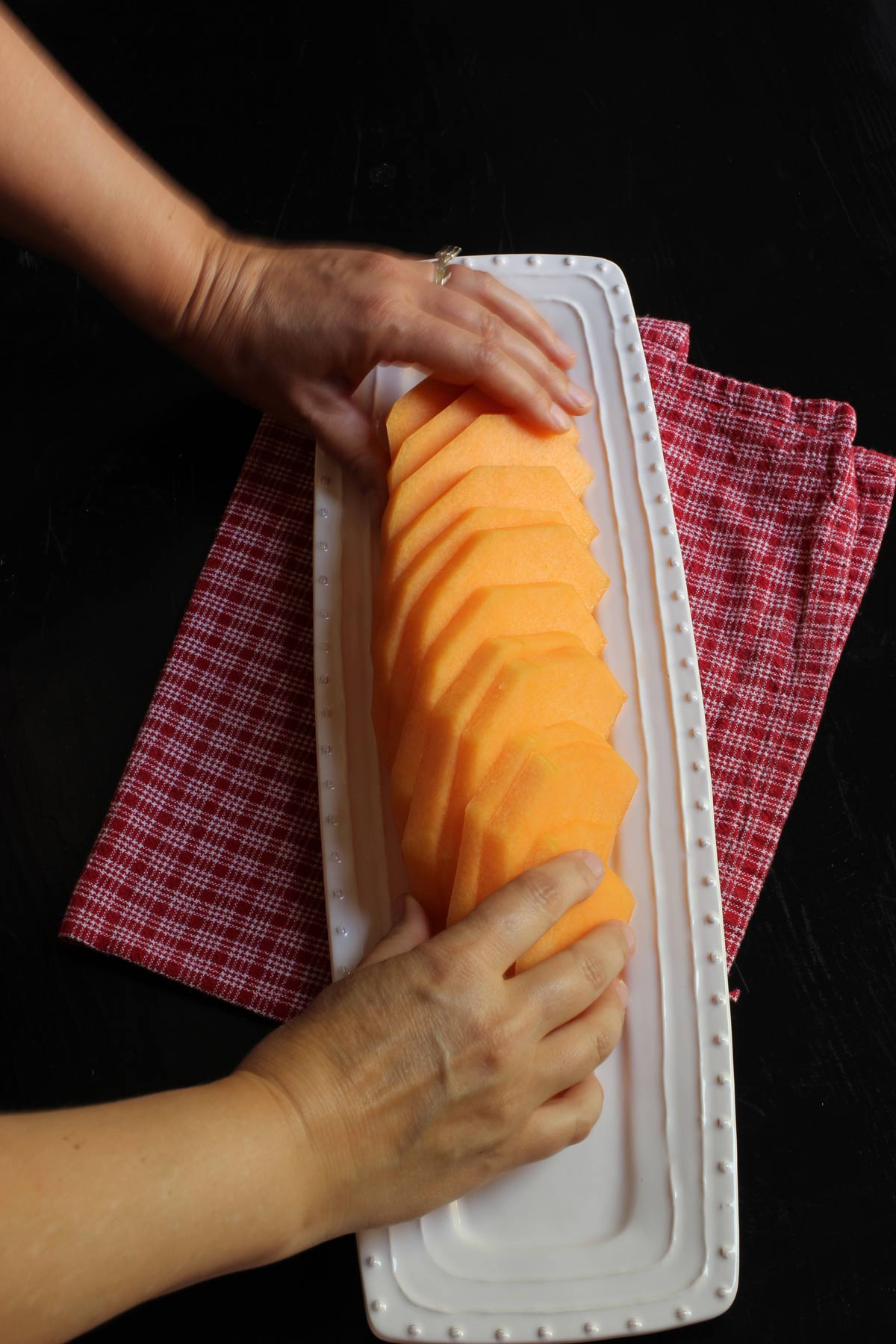 fanning melon slices on fruit tray.