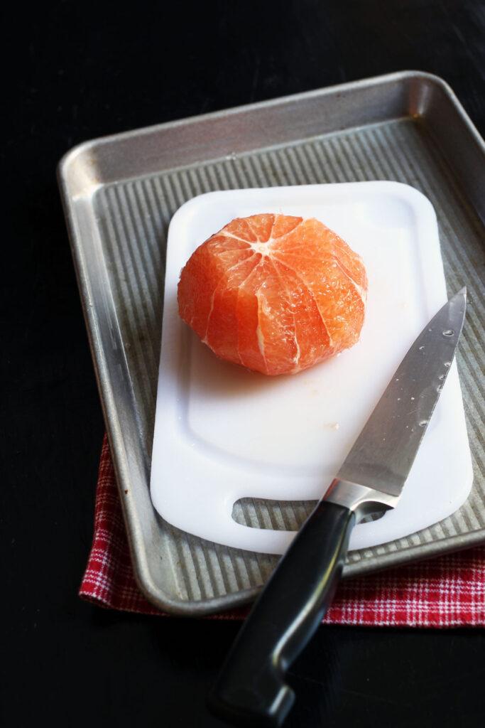 grapefruit with peel cut away sitting on cutting board.