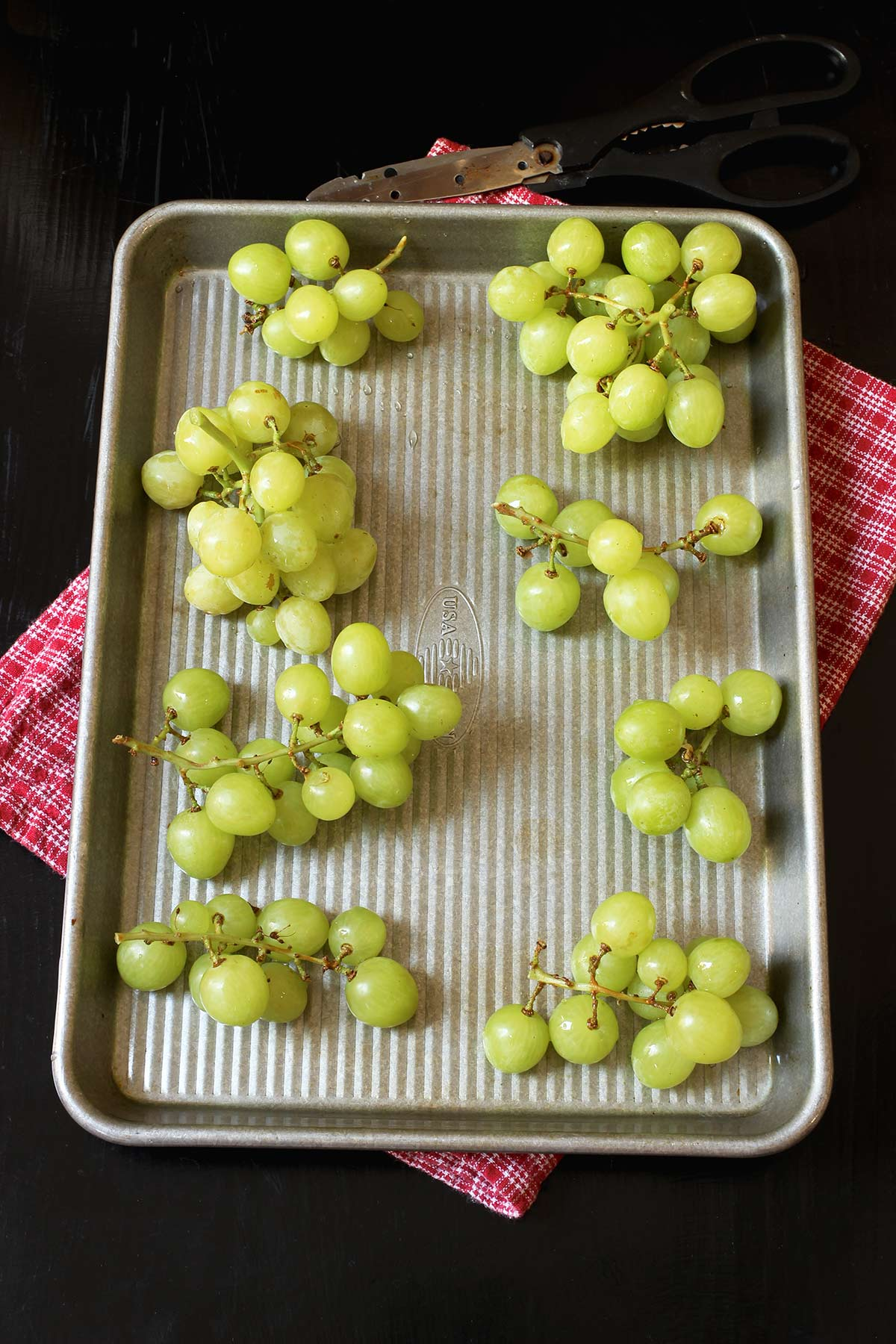 grape clusters laid out on small sheet pan atop a red cloth.
