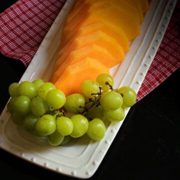 green grapes and cantaloupe on a white serving platter.